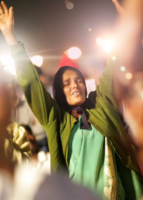 Woman in India prays at Benny Hinn Ministries Event